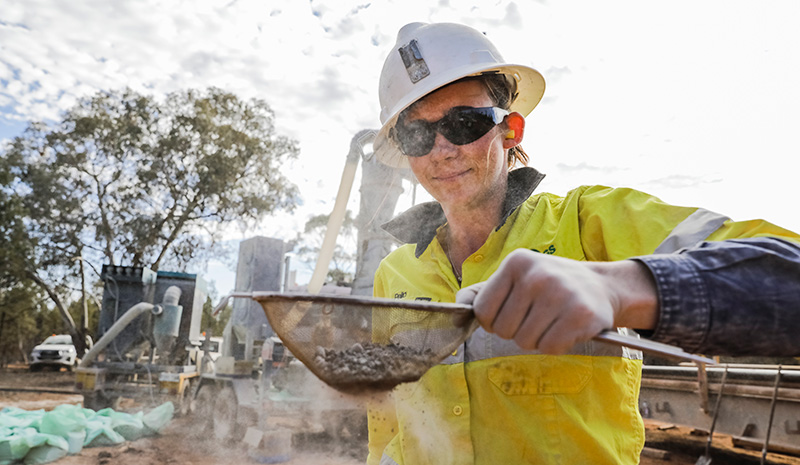 Woman wearing hard had holds sieve of gravel at a mine site